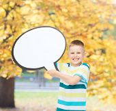 happiness, child, conversation and people concept - smiling little boy with blank text bubble over a