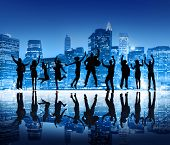 Group Of Happy Business People Silhouettes Jumping For Celebration On Cityscape Background