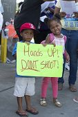 FERGUSON, MO/USA -AUGUST 15, 2014: Children hold sign at the Site of Quick Trip after Police Chief Thomas Jackson release of the name of the officer that shot Michael Brown.