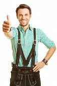 Happy bavarian man in leather pants holds his thumbs up