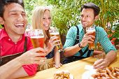 Laughing friends drinking beer together in a garden in summer