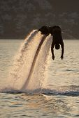 Flyboarder Silhouetted In Dive Towards Evening Sea