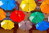 Floating umbrellas and city building on background.