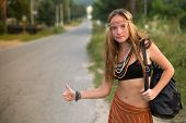 Young lovely hippie girl hitchhiking on countryside road.