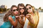 Three stylish girlfriends in sun glasses send air kiss to camera