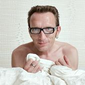 Pleased handsome naked man in bed under the white quilt sincerely with inviting smile