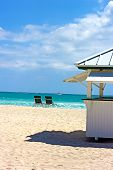 Sailboats at sea and empty chair on the beach.