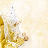 stock photo of christmas angel  - Golden wrapped christmas presents with an white angel on wooden background - JPG