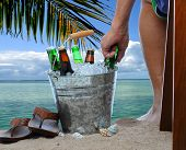 Closeup of a man sitting in a chair at a tropical beach reaching into a bucket filled with ice cold