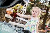 Cute Little Preschooler Girl Playing With A City Fountain