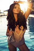 Sexy Girl With Dark Hair In Fashion Swimsuit Posing In Swimming Pool