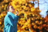 Woman Having Fun Blowing Bubbles In Autumnal Park