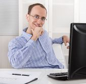 Satisfied Businessman Sitting In His Office With Computer.