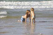 Two happy little girls having fun on the beach.