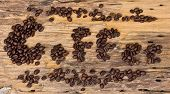 Inscription Of Coffee From Coffee Beans On Wood Background