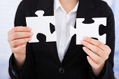 Businesswoman Joining Jigsaw Pieces