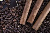 three cigars are on the grains of black coffee