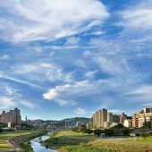 City scenery of park and river under blue sky and white clouds in Taipei, Taiwan.