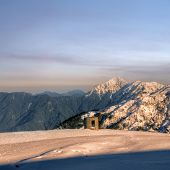 Beauty of snow mountain with blockhouse in yellow sunset.