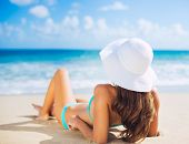 Beach vacation. Beautiful young woman in sun hat relaxing on the beach.
