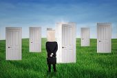 foto of anonymous  - Anonymous businessman standing in front of opportunity doors on the green field - JPG