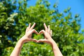 Young girl holding hands in heart shape framing on nature background
