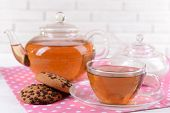 Teapot and cup of tea on table on brick wall background