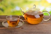 Teapot and cup of tea on table on bright background