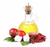 Sun dried tomatoes, feta cheese, olive oil in bottle and basil leaves isolated on white