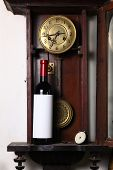 stock photo of pendulum clock  - Bottle of red wine with blank label template standing inside an old clock - JPG