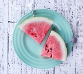 Slices of watermelon in plate on wooden background