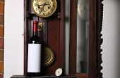 image of pendulum clock  - Bottle of red wine with blank label template standing inside an old clock - JPG