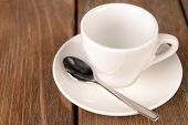 Empty cup with tea spoon on wooden background