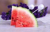 Slices of watermelon on cutting board and flowers on wooden table on natural background