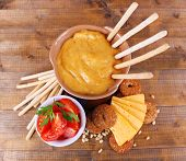 Fondue, slices of cheese, tomatoes and biscuits on wooden background