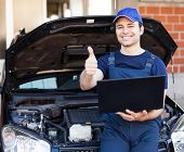 Happy mechanic using a laptop computer to check a car engine