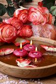 foto of unity candle  - Spa concept with roses pink salt and candles that float in a wooden bowl with water - JPG