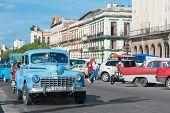 HAVANA, CUBA - JANUARY 8, 2015 : Street scene with people and traffic on a beautiful sunny day in Old Havana