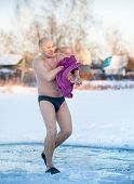 man wipes a towel after swimming in  water at frosty morning