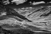 Himalayan valley landscape with road near Kunzum La pass - allegedly the highest motorable pass in the world (5602 m), Ladakh, India. Black and white version