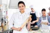 Portrait of smiling female chef holding rolling pin while colleagues preparing pasta at commercial kitchen