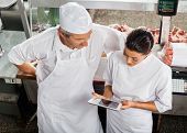 High angle view of male and female butchers using digital tablet in store