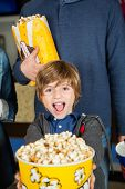 Portrait of excited boy showing popcorn while father standing in background at cinema