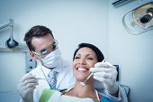 foto of dentist  - Male dentist examining womans teeth in the dentists chair - JPG