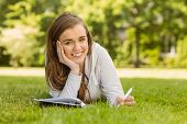 Smiling university student lying and writing on notepad in park at school