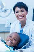 picture of dentist  - Portrait of female dentist examining a boys teeth in the dentists chair - JPG