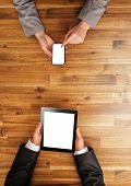 Man and woman working on mobile devices. Shot from above view