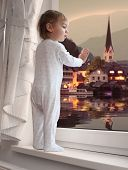 Little boy looking at beautiful evening view from a window.