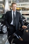 stock photo of only mature adults  - Mature grey hair businessman choosing a new car - JPG