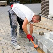 A Worker Creates A Terrace Of Concrete Paving Stones.